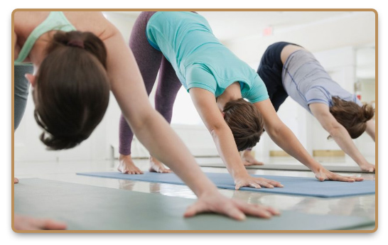 Group doing Hatha yoga exercises in yoga class on mats