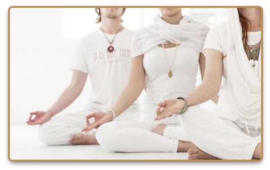 A group practices Kundalini yoga in white clothes to unlock the serpent power