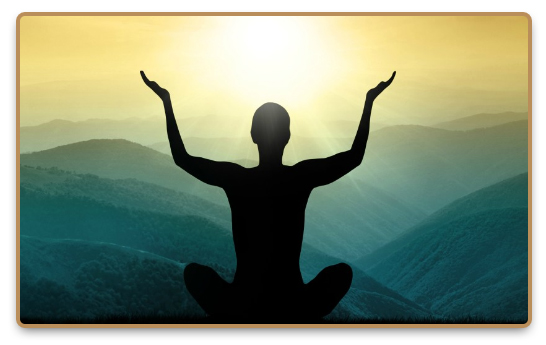 Man meditates in the mountains with his hands held up in the sunshine