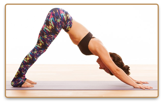 Woman practicing Vinyasa yoga, performing downward dog yoga pose