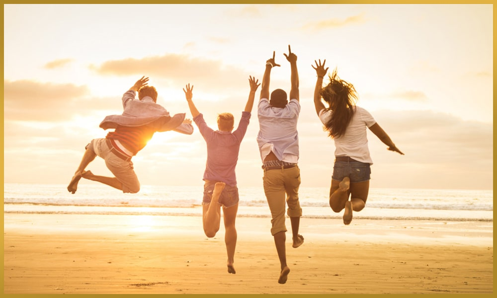 Happy group full of vitality jumping on the beach in the sand in sunshine
