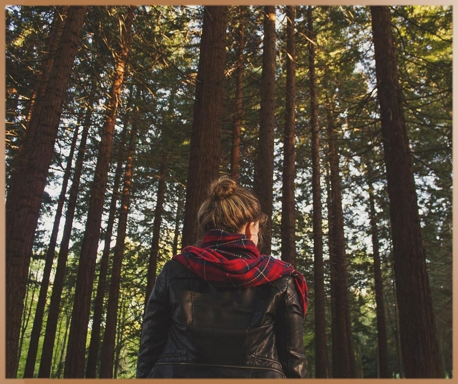 Woman in a forest is watching the trees in a scarf and leather jacket
