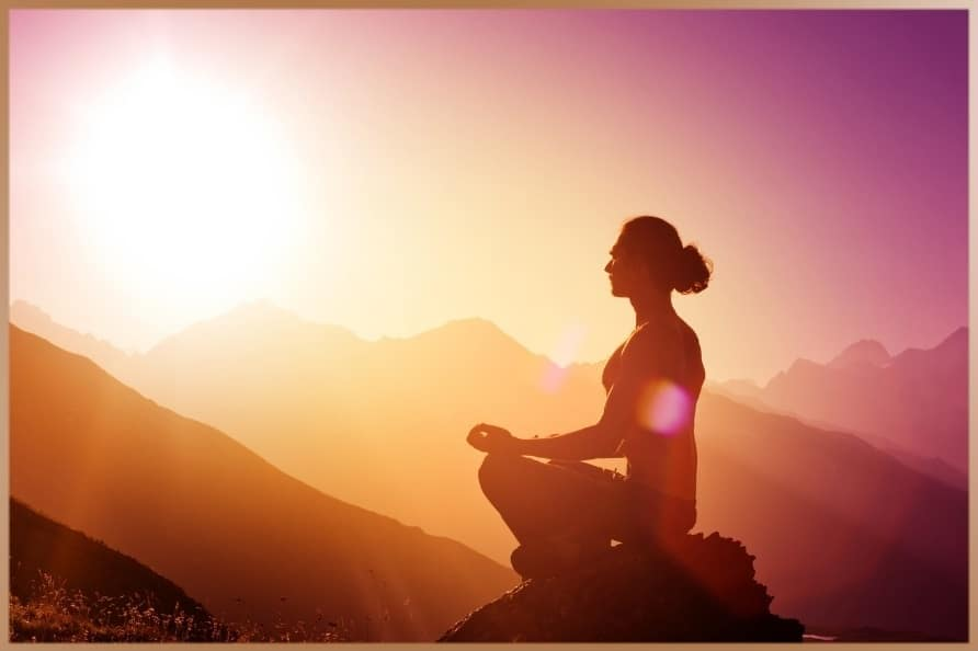 Woman meditates between the mountains in the sunset