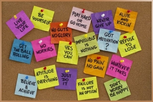 Positive thoughts written on post its pinned to a board as mantras for motivation