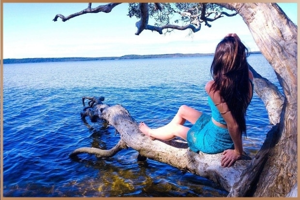 Happy woman watching a blue lake on a tree