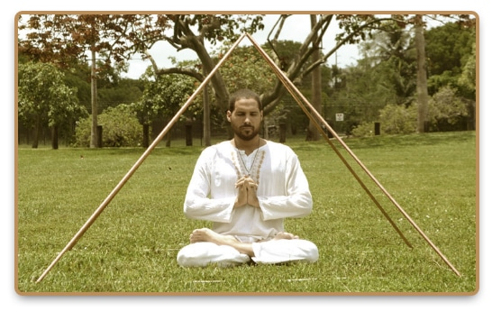Man practicing pyramid meditation while sitting under a pyramid structure