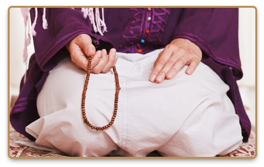 Man practices Sufi meditation with a mala in his hand