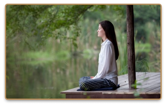 Relaxed woman meditating on the shore of the lake under a tree