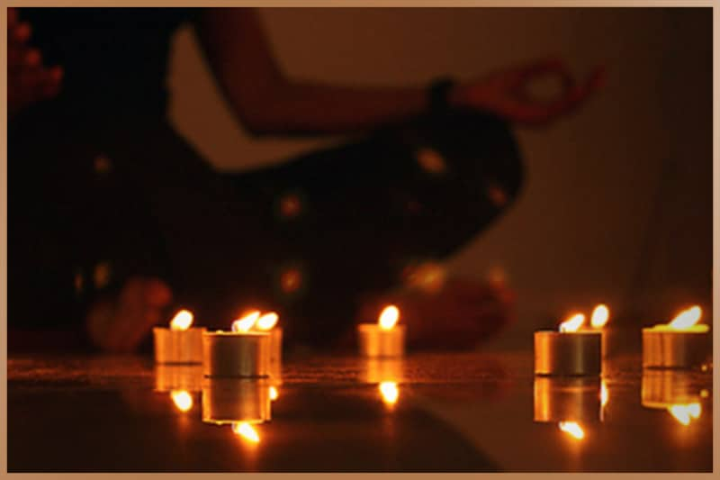 Meditation practice in a dark room with candles